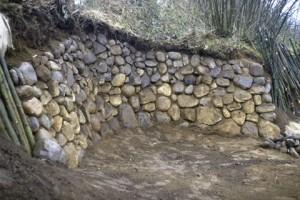 Hangsicherung mit Trockenmauer und Lebendverbau von Weiden. Die Feldsteinmauer dient gleichzeitig als Wärmespeicher - zum Sitzen in den Abendstunden.